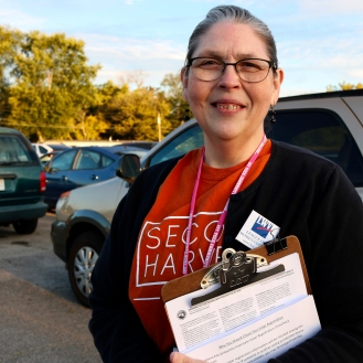 """Nancy McWilliams hands out information on voting registration to people lined up in cars during the Second Harvest food tailgate on Sept. 28 in Muncie, IN. McWilliams volunteers with Second Harvest on the poverty elimination team. """"To see this many people who are up at this time of the day so that they can get extras for their house is just amazing,"""" McWilliams said, """"amazingly awful."""""""